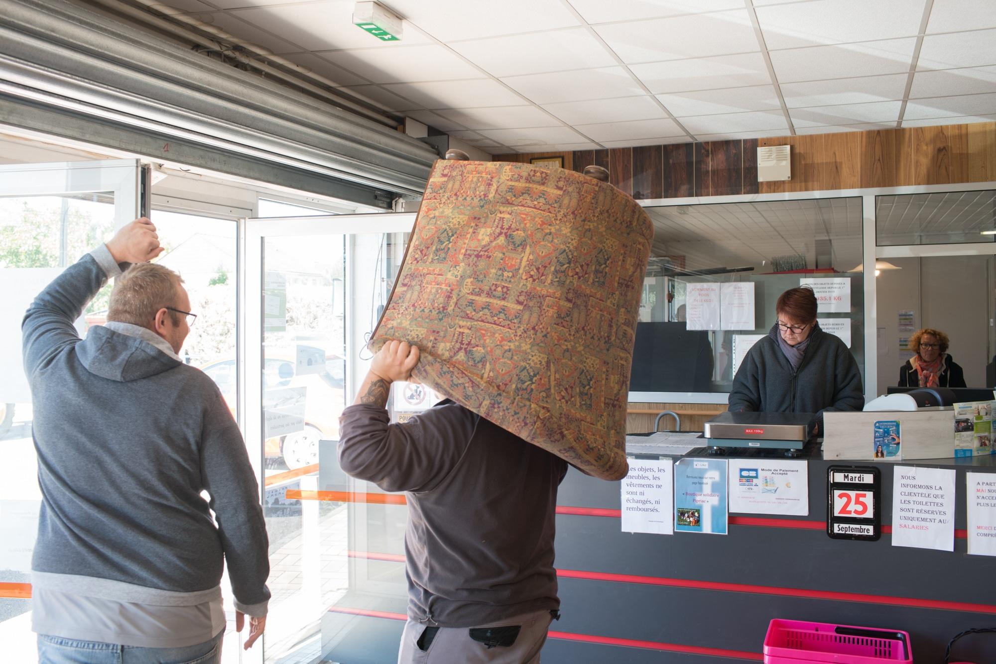 Nathalie, derrière la caisse. Au premier plan, un homme transporte un fauteuil vers l'extérieur.