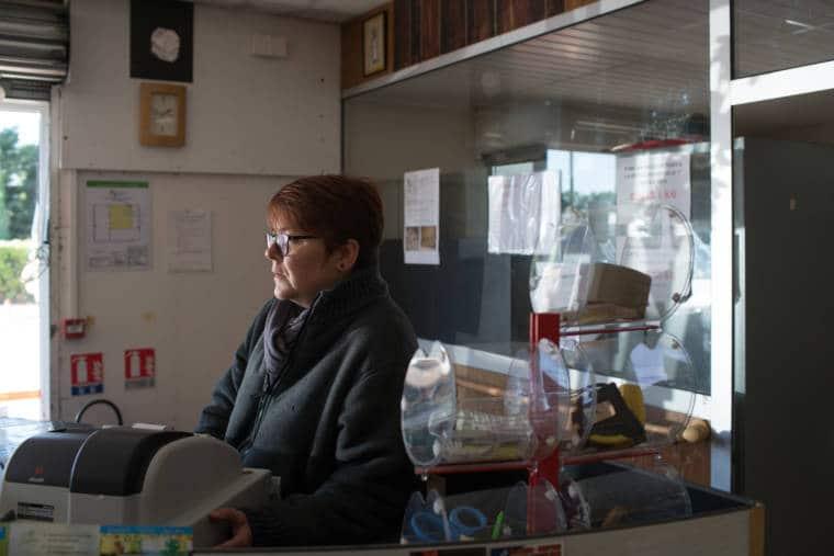 Portrait de profil de Nathalie, à la caisse.