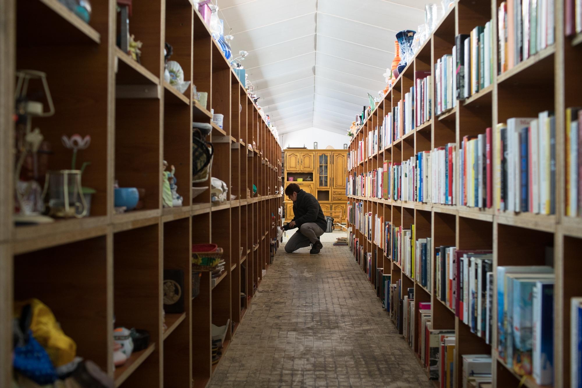 Au bout d'un couloir constitué de deux grandes bibliothèques ornées d'objets décoratifs et de livres, Nathalie, accroupie, range un accessoire.