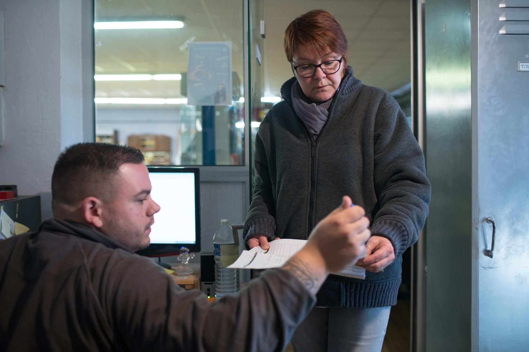 Nathalie consulte un tableau imprimé. Au premier plan on aperçoit un collègue de travail.