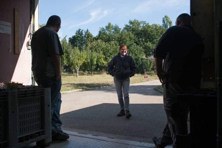 Nathalie, à l'extérieur, souriante, échange avec deux personnes au premier plan.