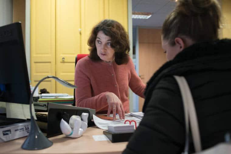 Patricia consulte son ordinateur. En face d'elle est assise une jeune femme.