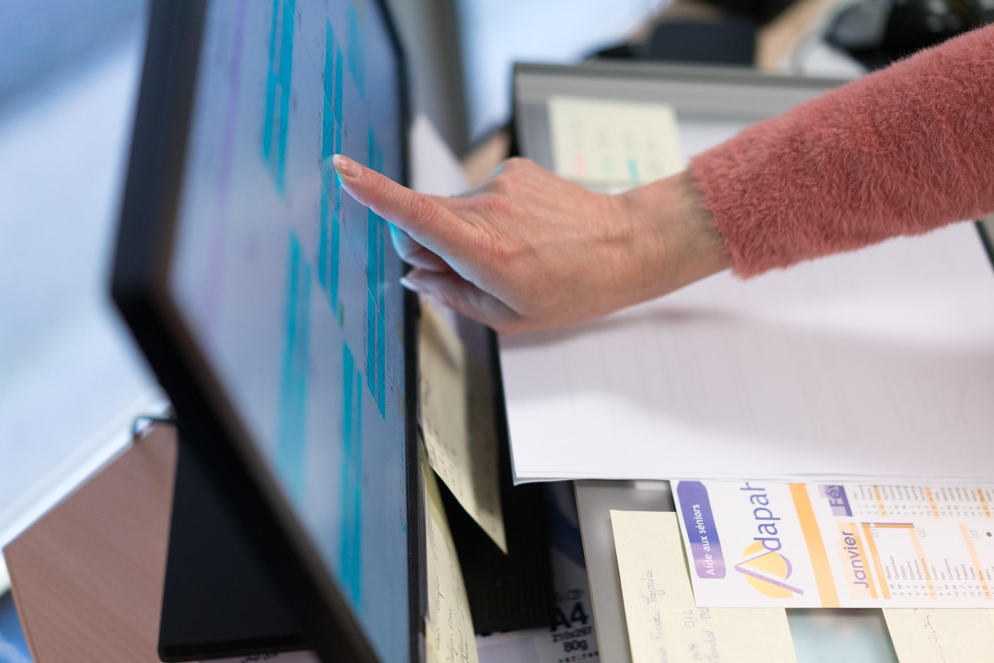 La main de Patricia touche son écran d'ordinateur, désignant un calendrier