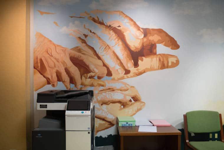 Une photocopieuse, une table basse et une chaise adossés à une fresque murale représentant des mains guidées par d'autres mains, avec différents niveaux de détails