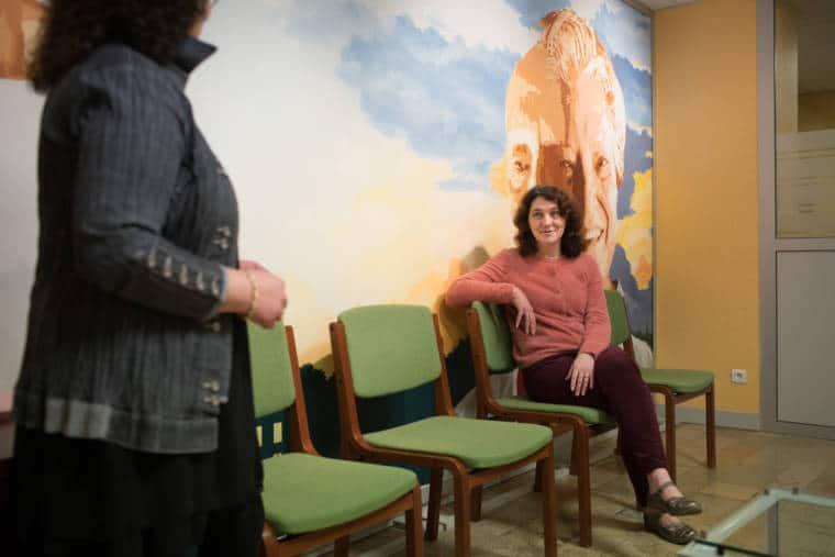 Patricia, souriante, est assise sur une des quelques chaises adossées à une fresque figurant deux visages d'hommes