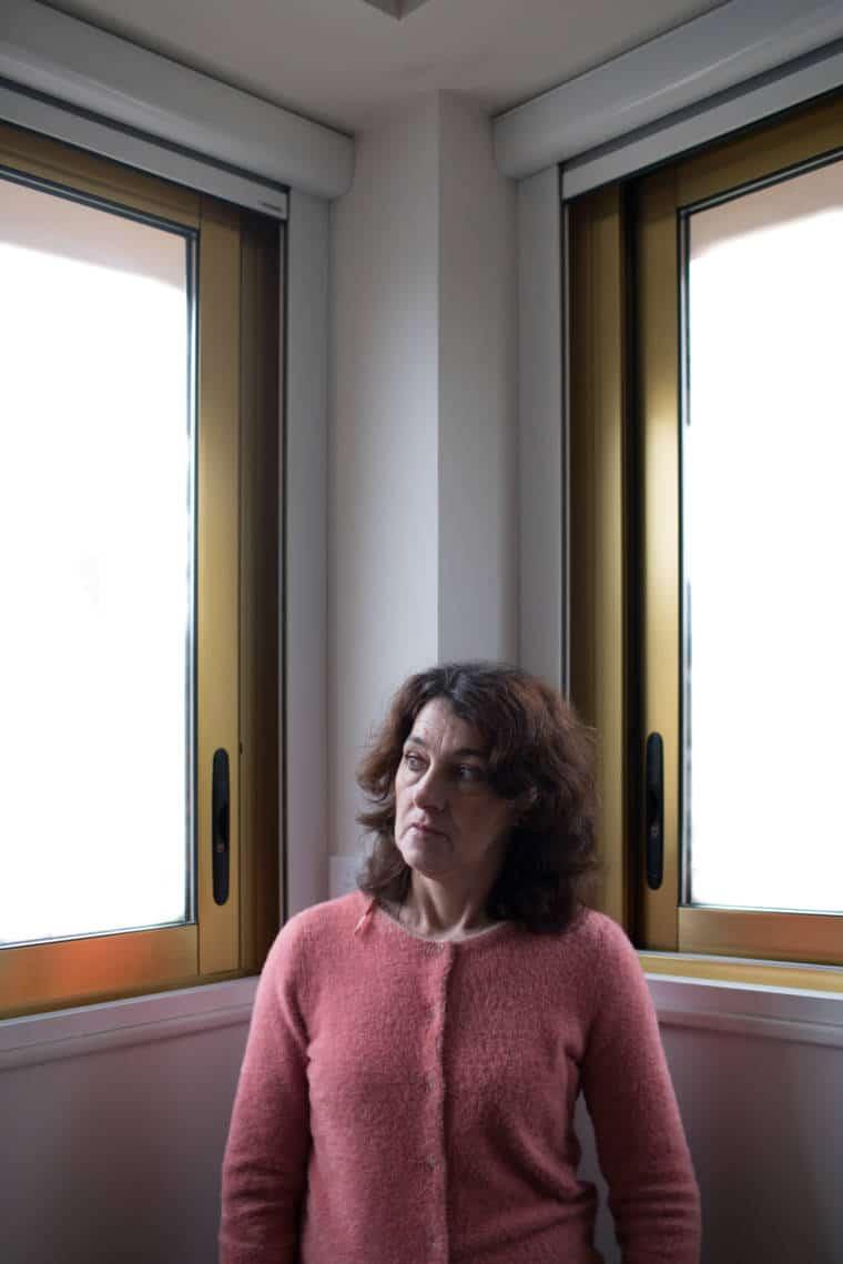 Patricia se tient entre deux fenêtres aux reflets dorés dans un bureau