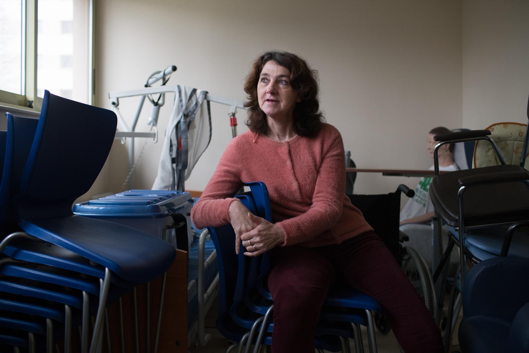 Patricia est assise dans une salle contenant du matériel de bureau et du matériel médical
