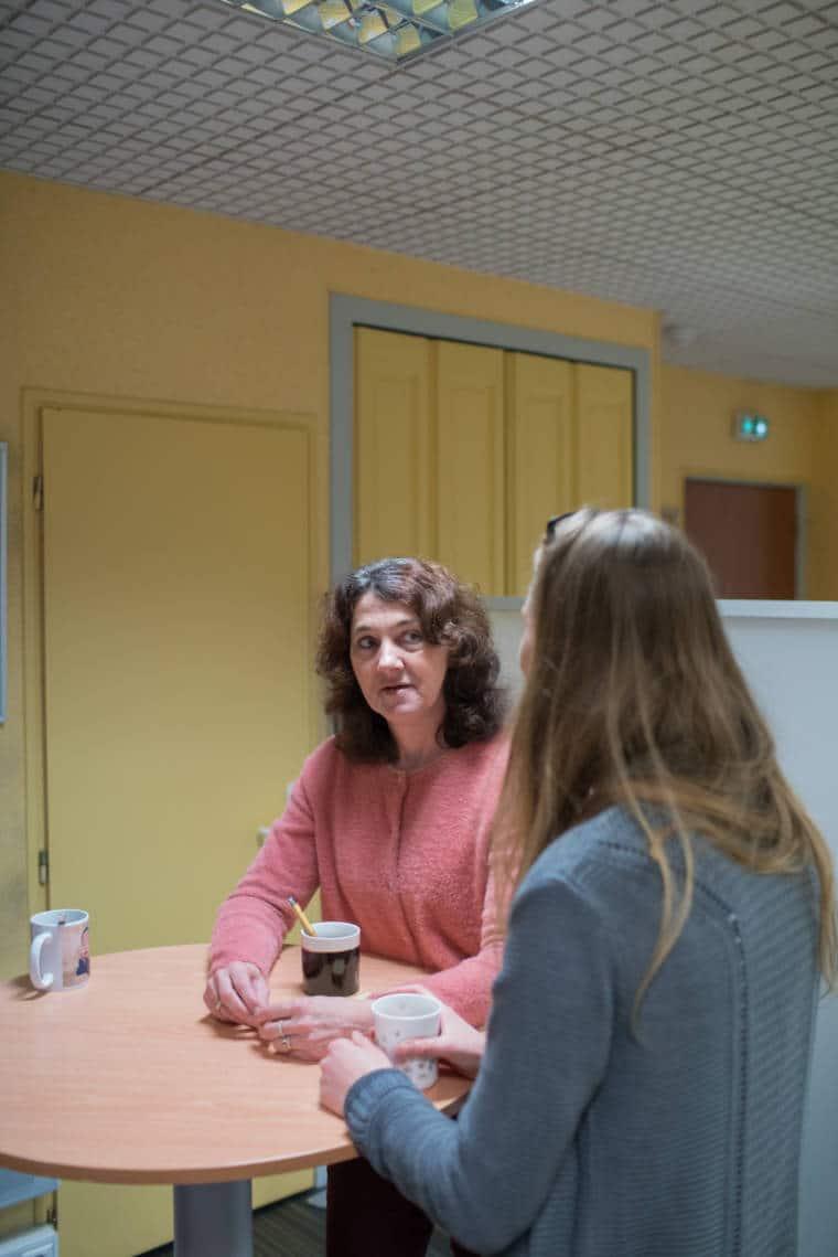 Patricia partage une tasse de café avec une collègue autour d'une table haute
