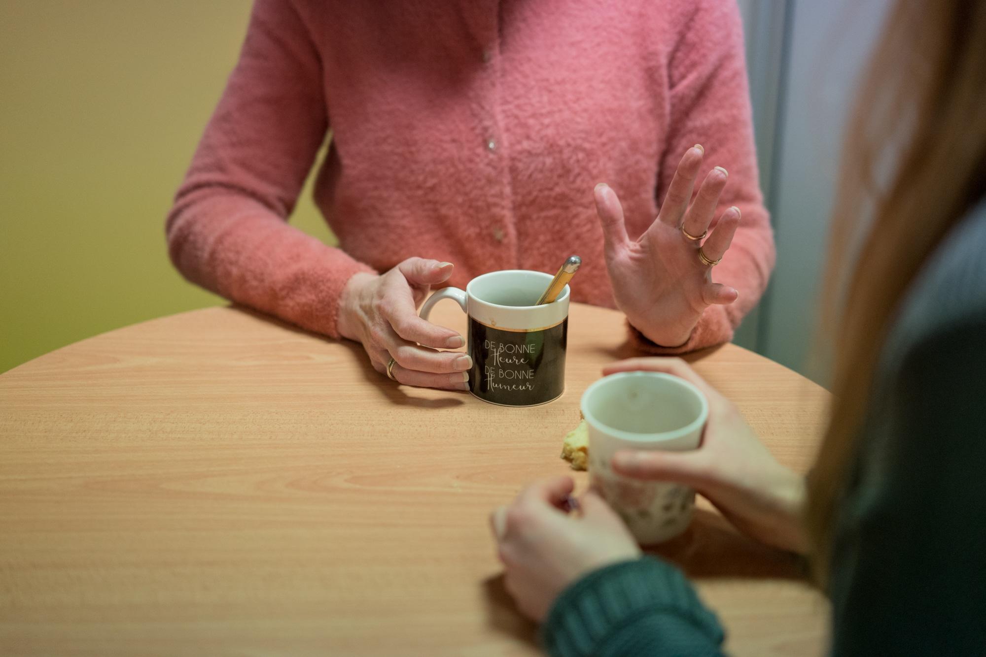 """Plan rapproché présentant les mains de Patricia et d'une collègue autour de deux tasses de café. Sur celle de Patricia on peut lire """"De bonne heure, de bonne humeur"""""""