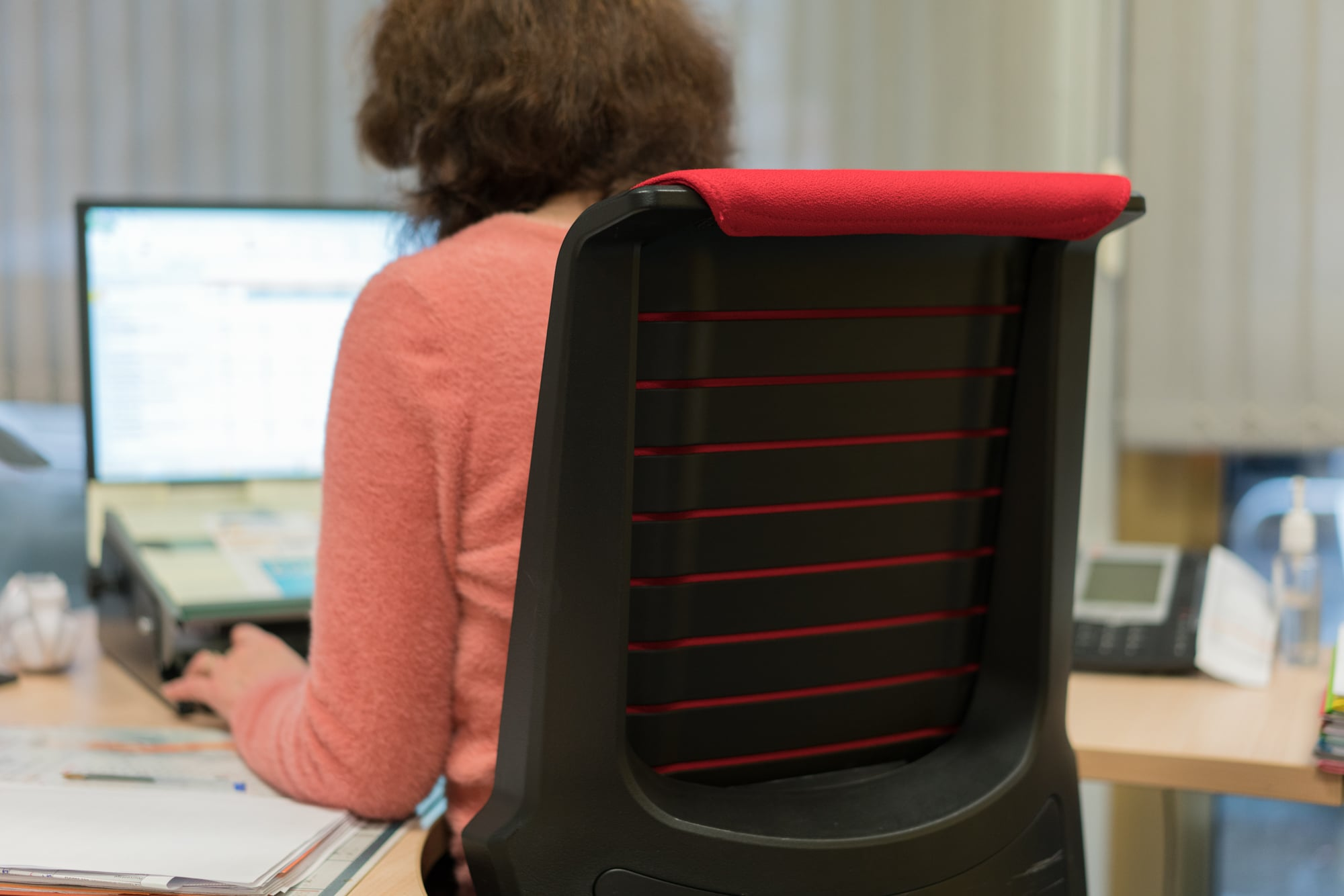 Patricia, de dos, est assise à son bureau, sur une chaise adaptée