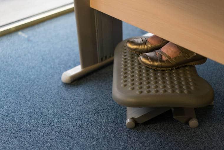 Les pieds de Patricia posés sur un repose-pieds sous son bureau