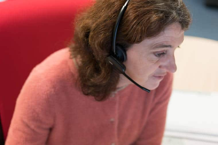 Patricia, penchée en avant, portant un casque de téléphonie