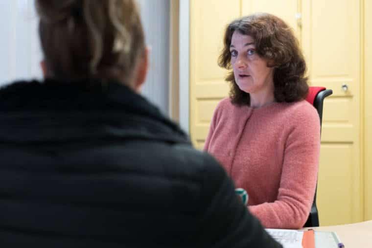 Patricia, de face, est assise à son bureau et discute avec une jeune femme