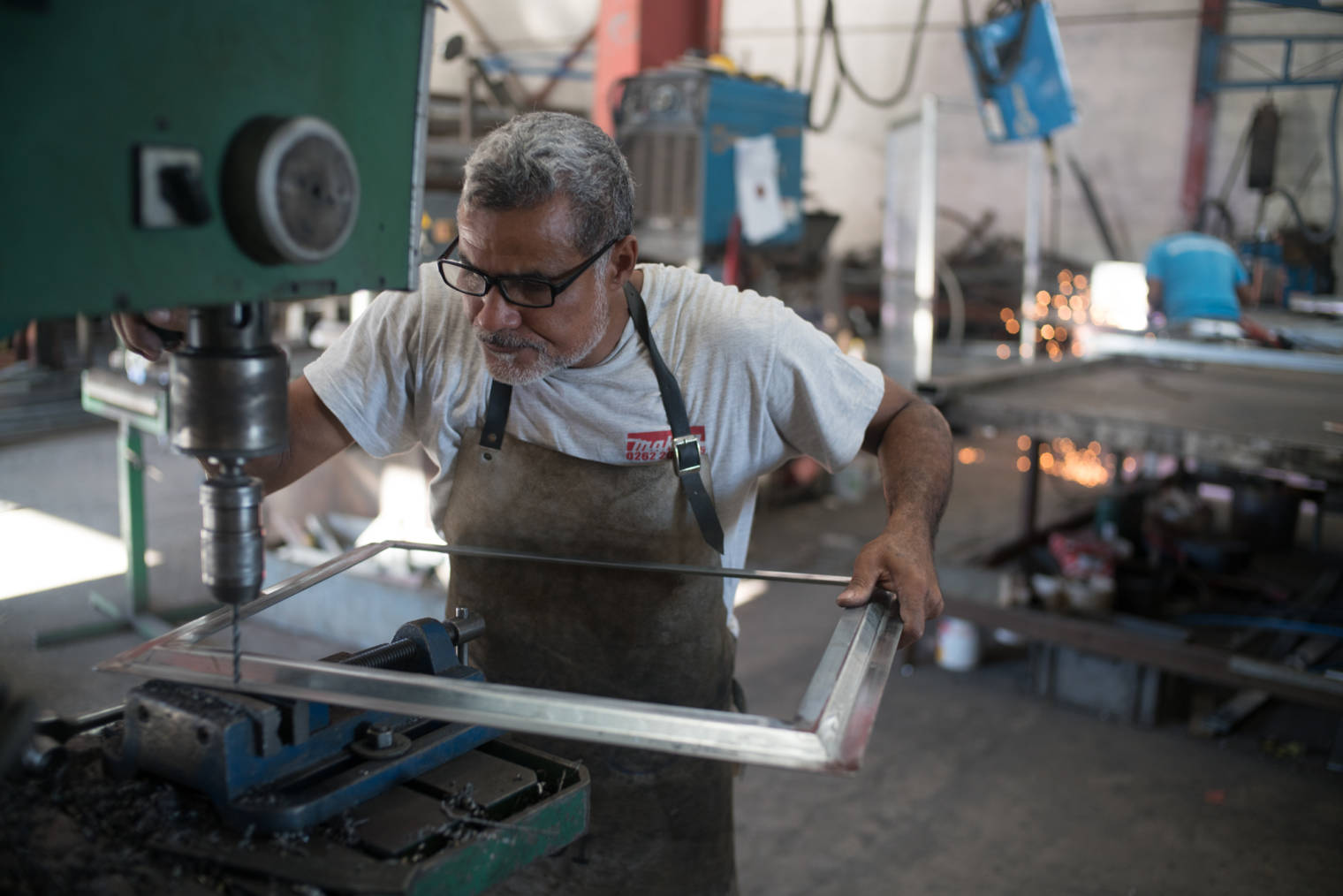 Jean-Claude travaille sur un cadre métallique avec une perceuse à colonne..