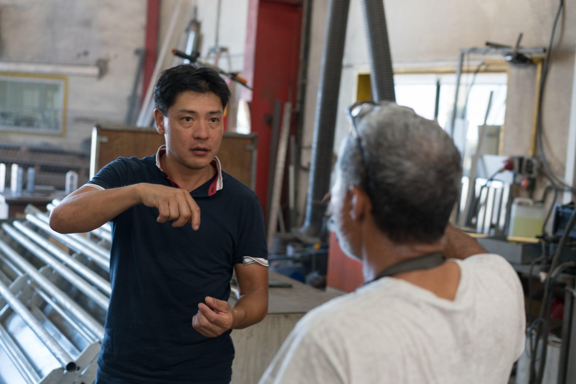 Jean-Claude communique avec un homme à l'aide de signes.