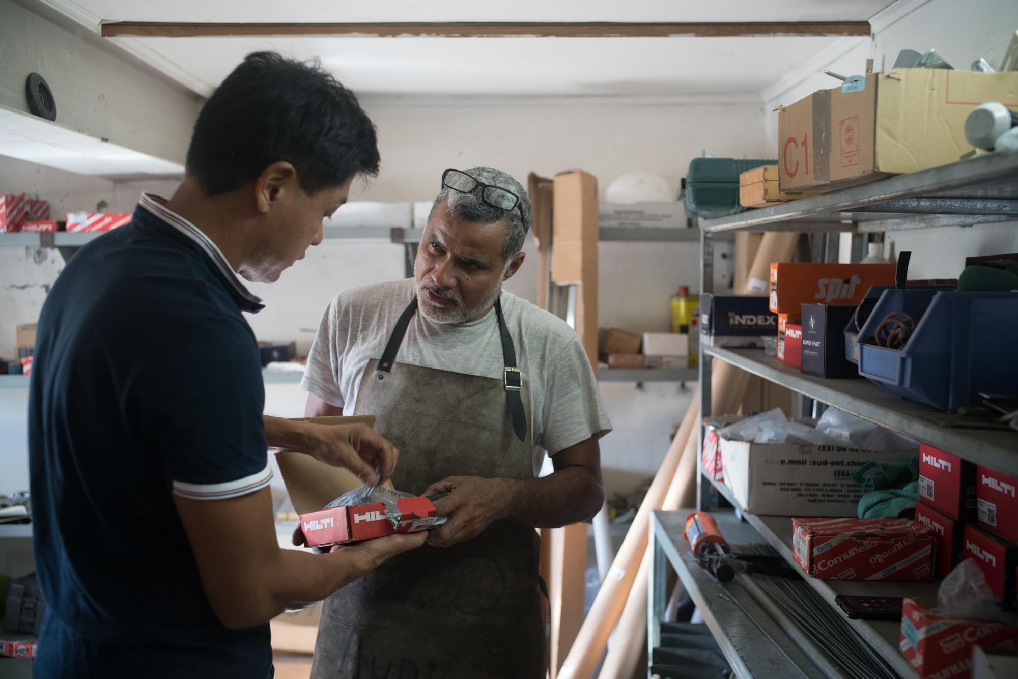 Jean-Claude et un autre homme discutent autour d'une boite de matériaux.