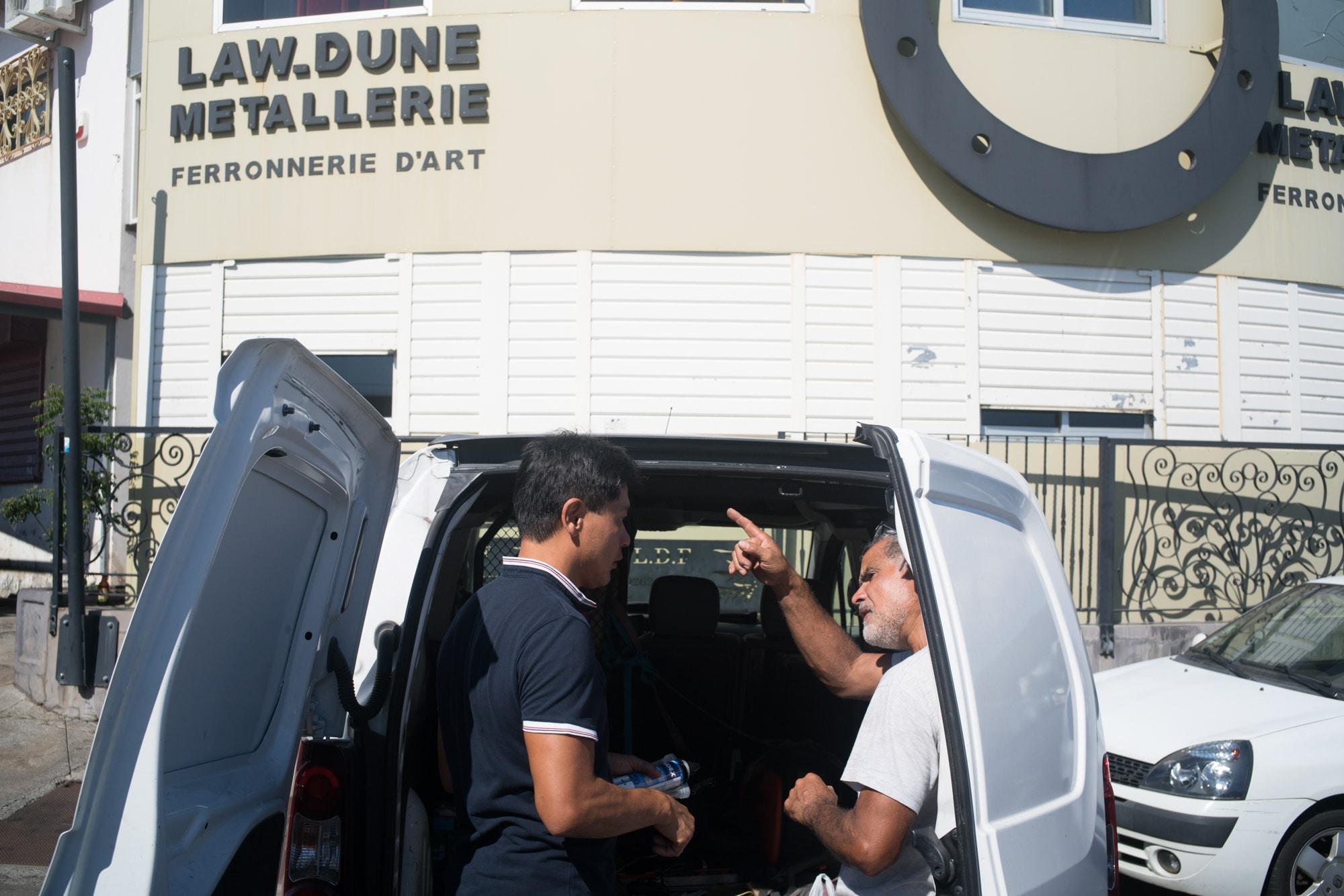 Jean-Claude discute avec un homme à l'arrière d'une camionnette. Au second plan on aperçoit l'enseigne Law Dune Metallerie Ferronerie d'Art..