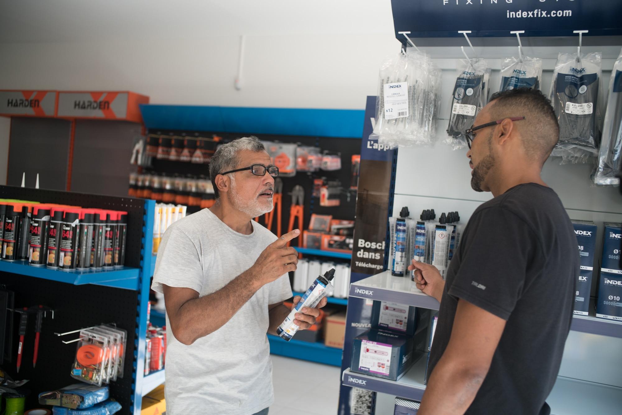 Jean-Claude, un tube à la main, s'adresse à un vendeur dans un magasin de matériaux.