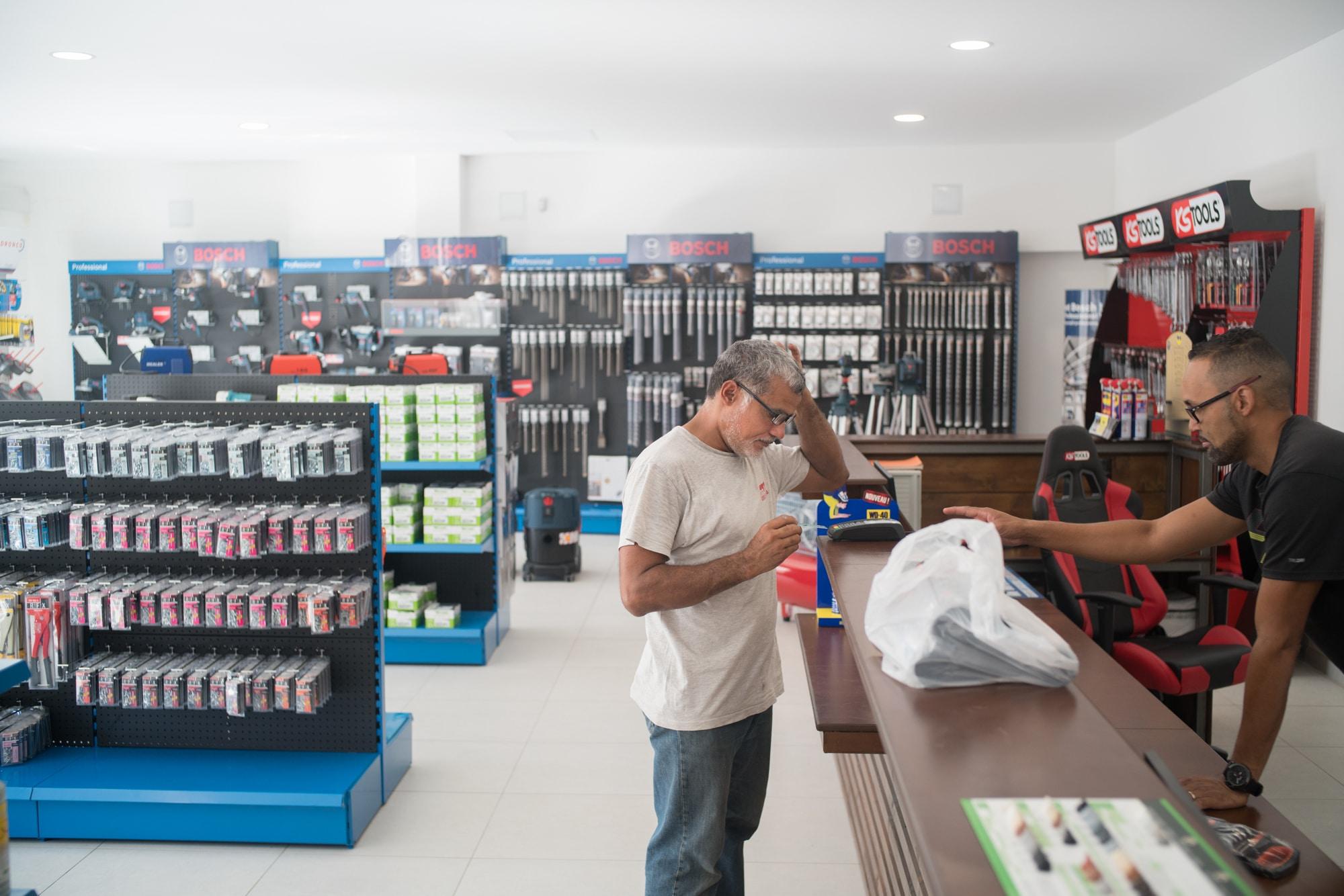 Jean-Claude finalise des achats à la caisse d'un magasin de matériaux.