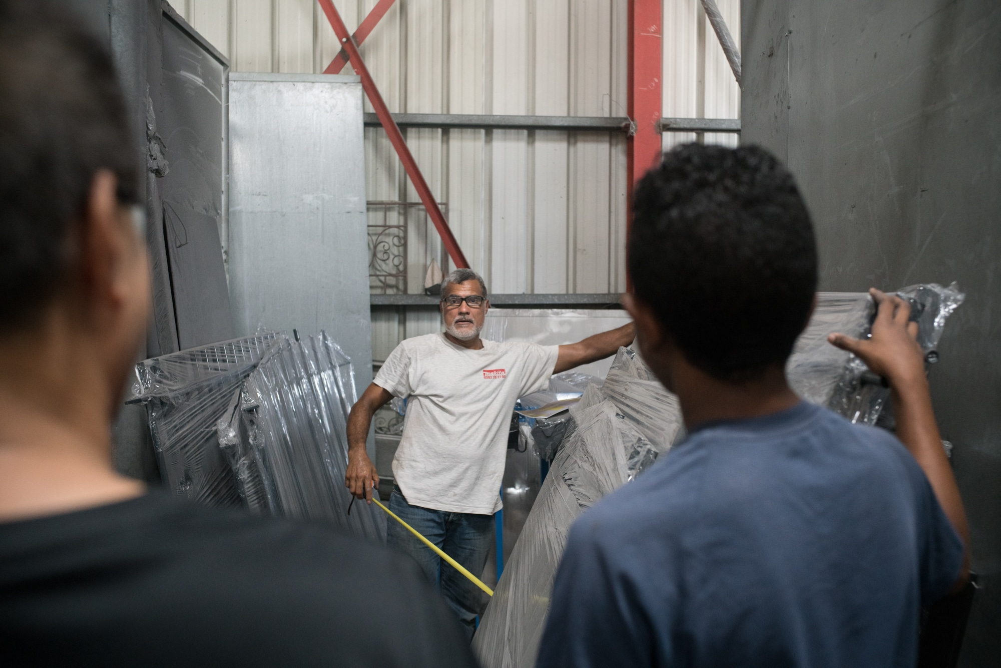 Jean-Claude, un mètre à la main, fait face à deux employés.