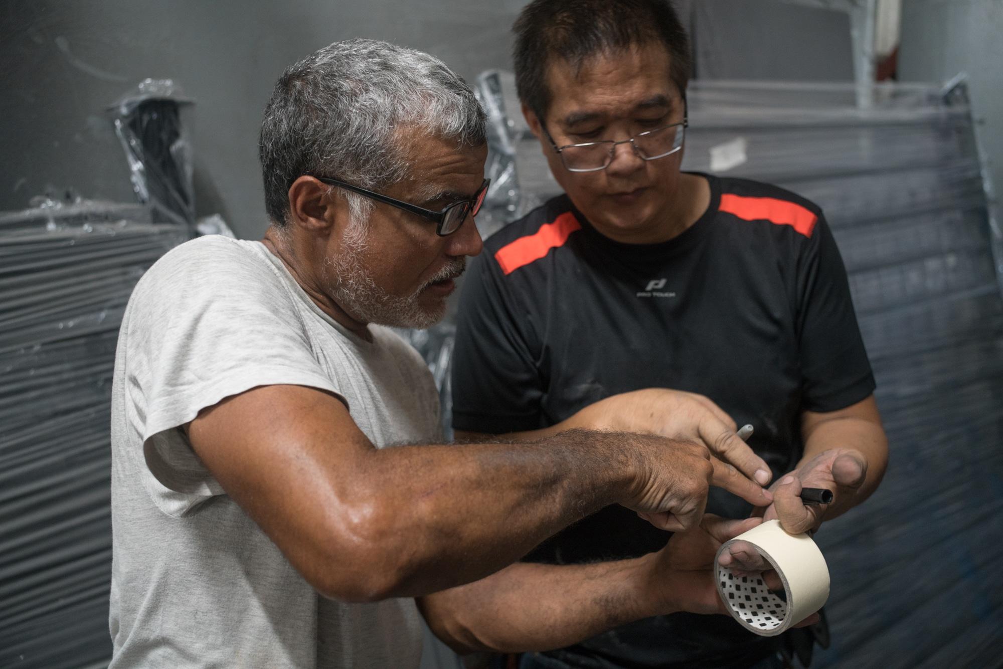 Jean-Claude montre à un homme la main de celui-ci, qui tient un stylo.