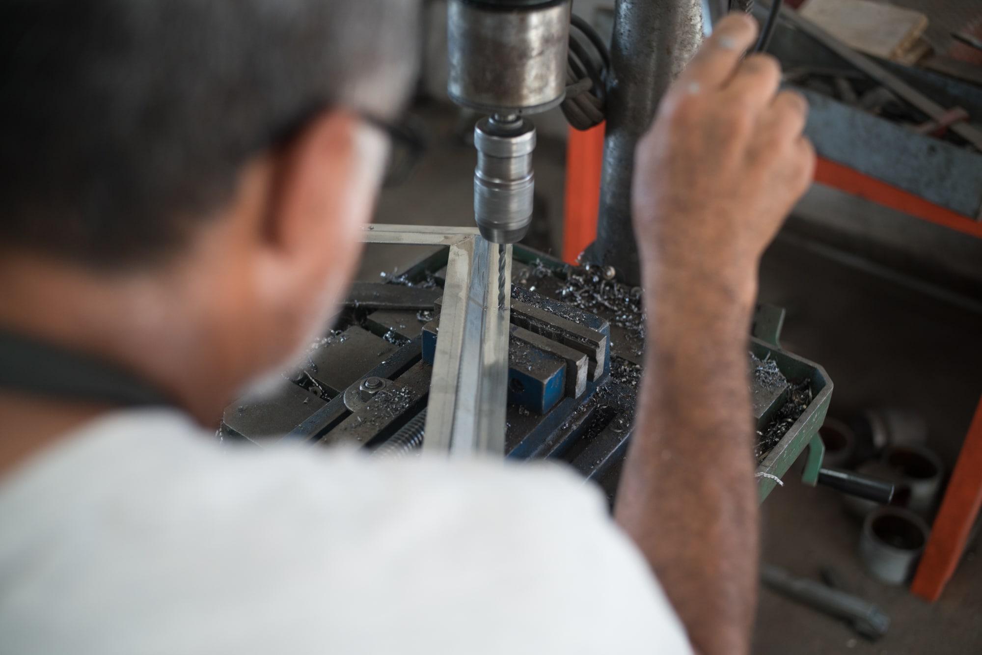 Jean-Claude perce un trou dans un cadre métallique à l'aide d'une perceuse à colonne..