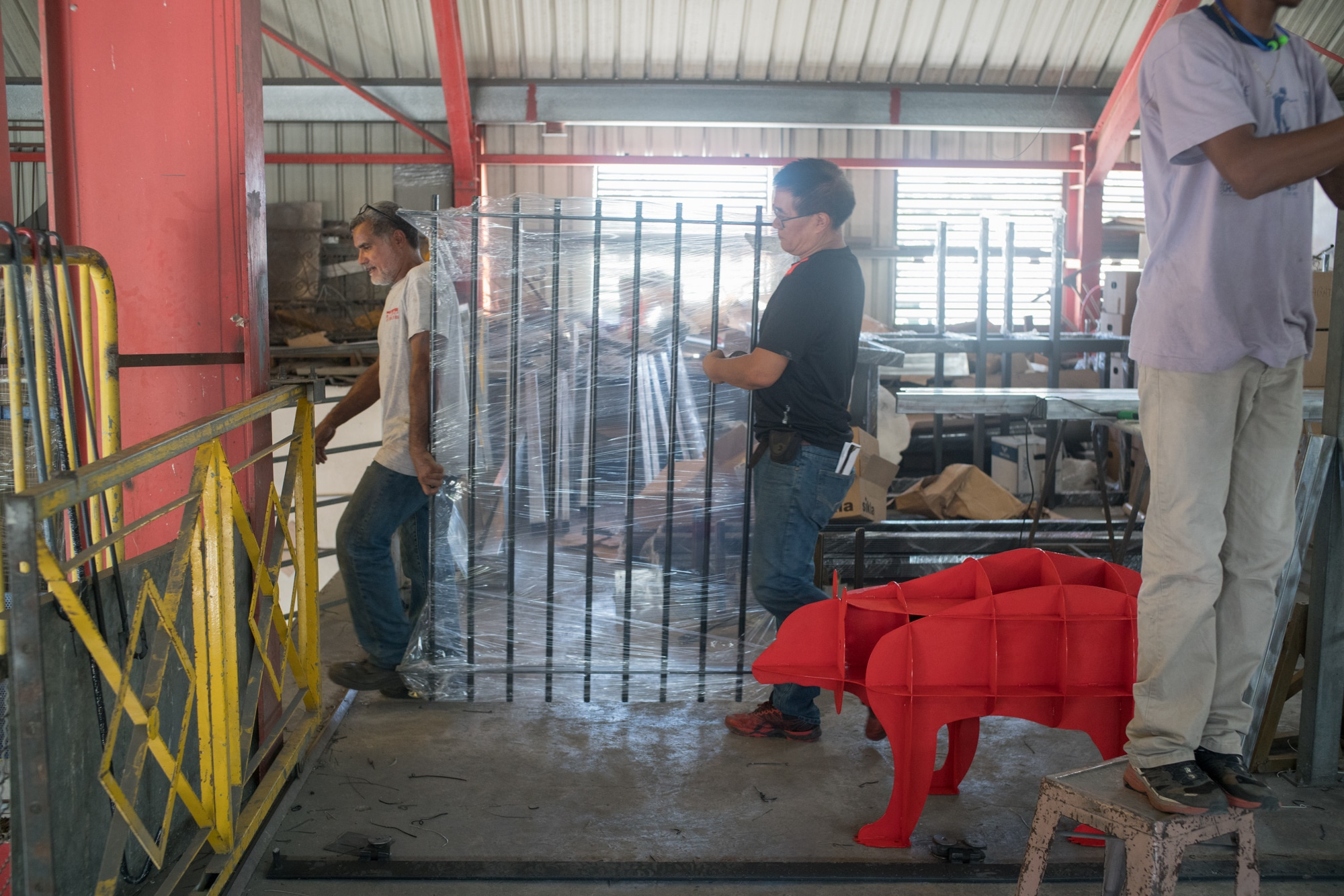 Jean-Claude transporte une barrière de métal avec un employé au sein de l'atelier.