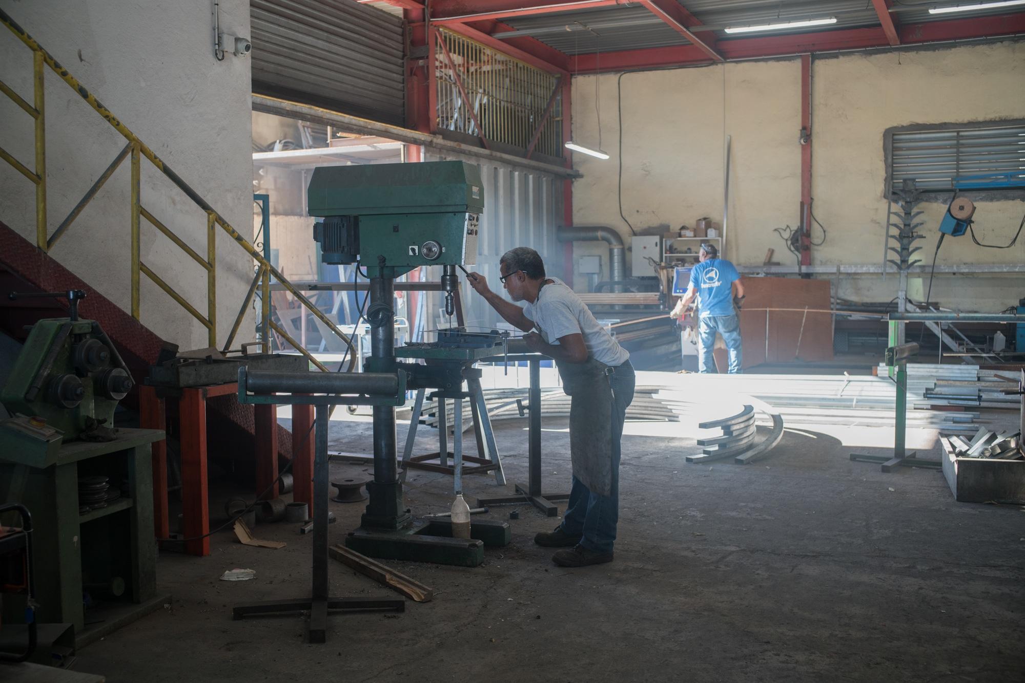 Jean-Claude perce un cadre métallique à l'aide d'une perceuse à colonne. Autour de lui on aperçoit un vaste atelier.