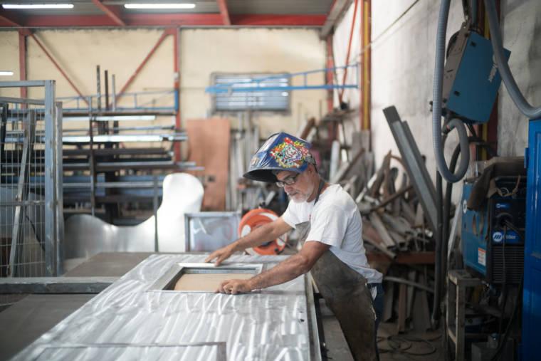 Jean-Claude positionne le cadre métallique dans une grande structure en métal. Il est coiffé d'un masque de soudeur orné d'un autocollant coloré.