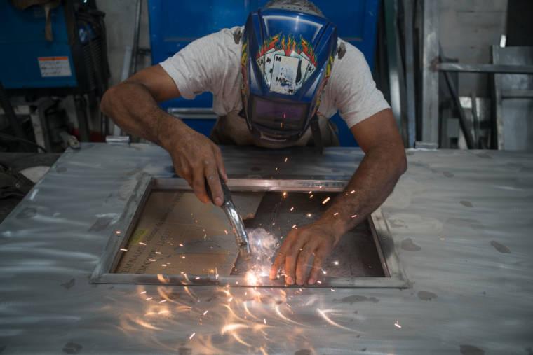 Jean-Claude soude le cadre dans la structure métallique.