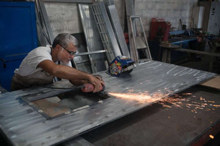 Jean-Claude utilise sa disqueuse sur la cadre métallique.