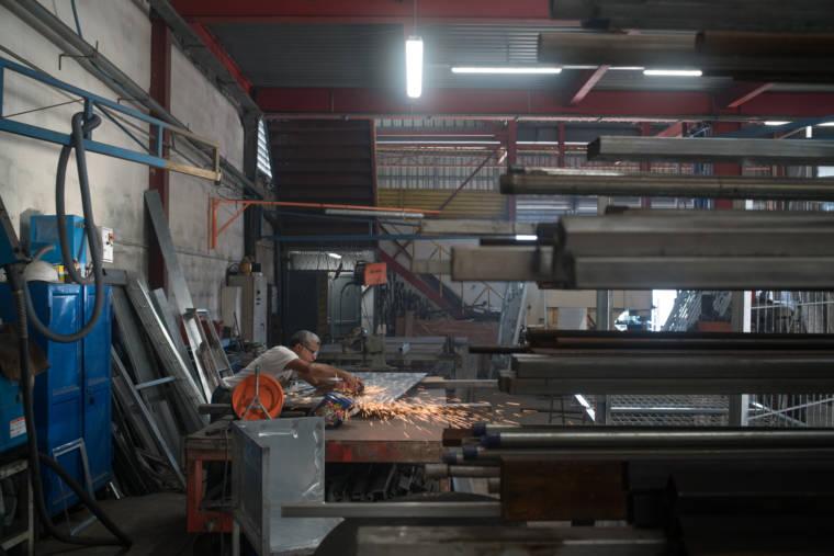 Jean-Claude utilise sa disqueuse sur la structure métallique. Au premier plan et autour de lui on distingue différentes structures et tiges métalliques.