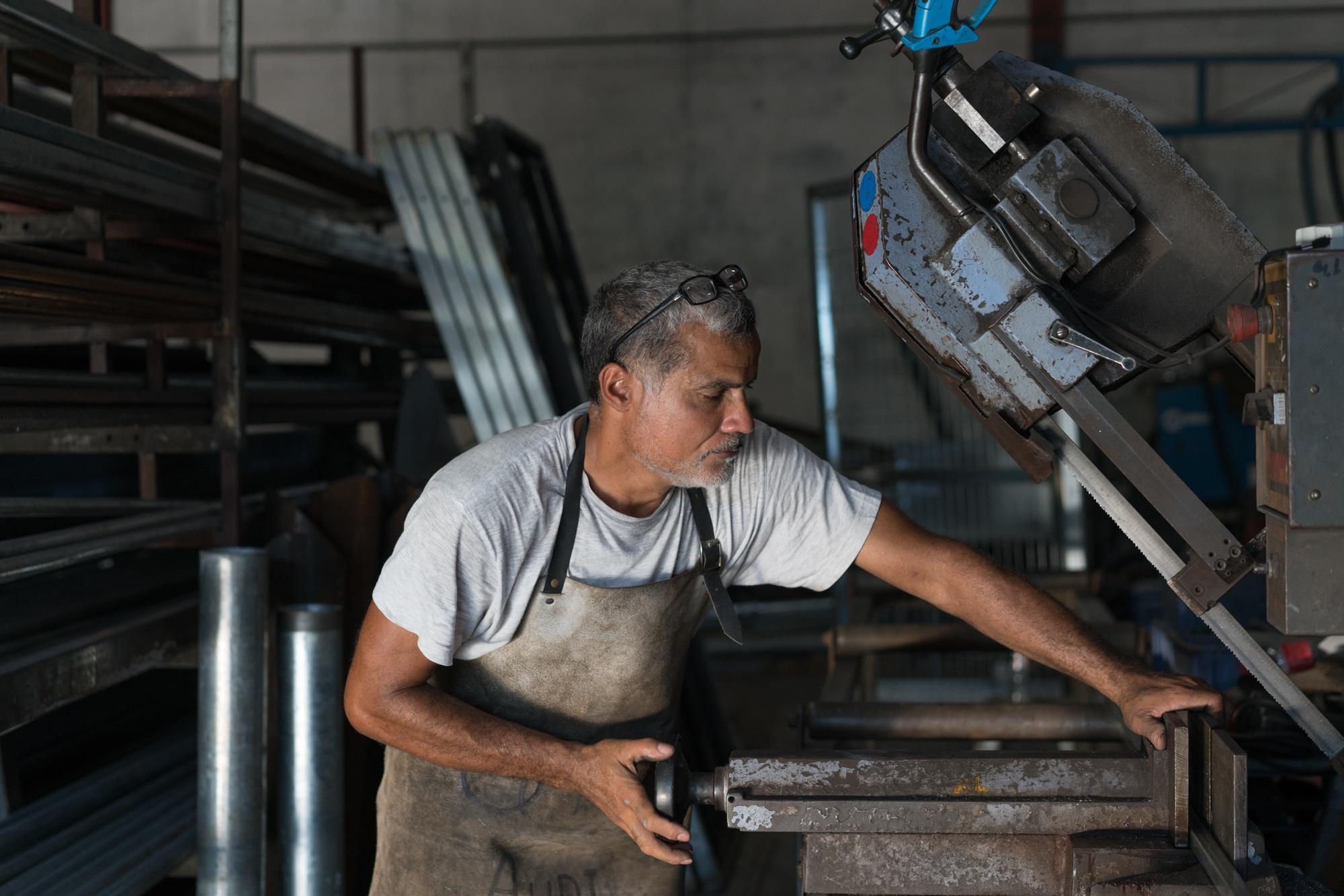 Jean-Claude ajuste un réglage sur une machine munie d'une scie.
