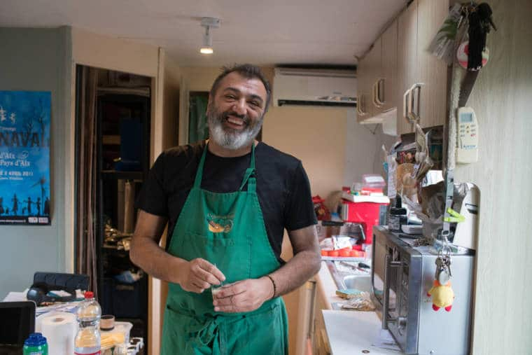 Pierre, dans sa cuisine, souriant. Il porte un tablier.
