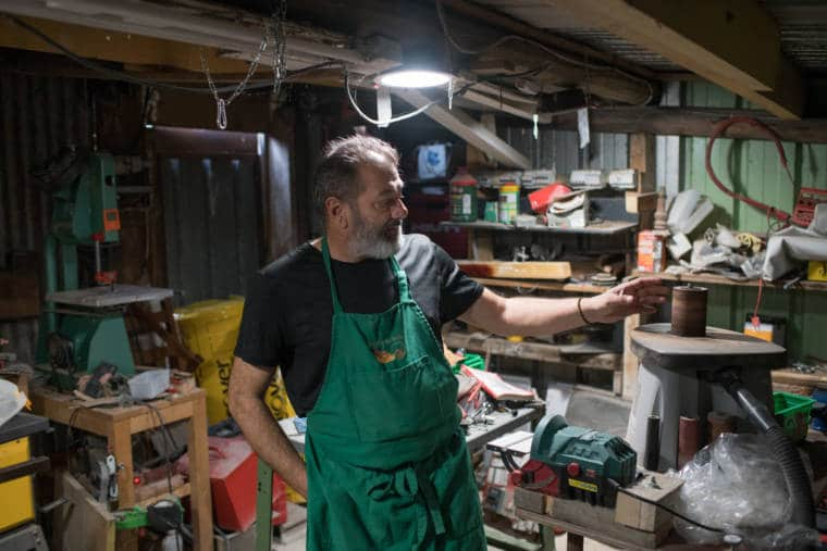 Pierre, au sein de son atelier, semble désigner quelque chose de la main.