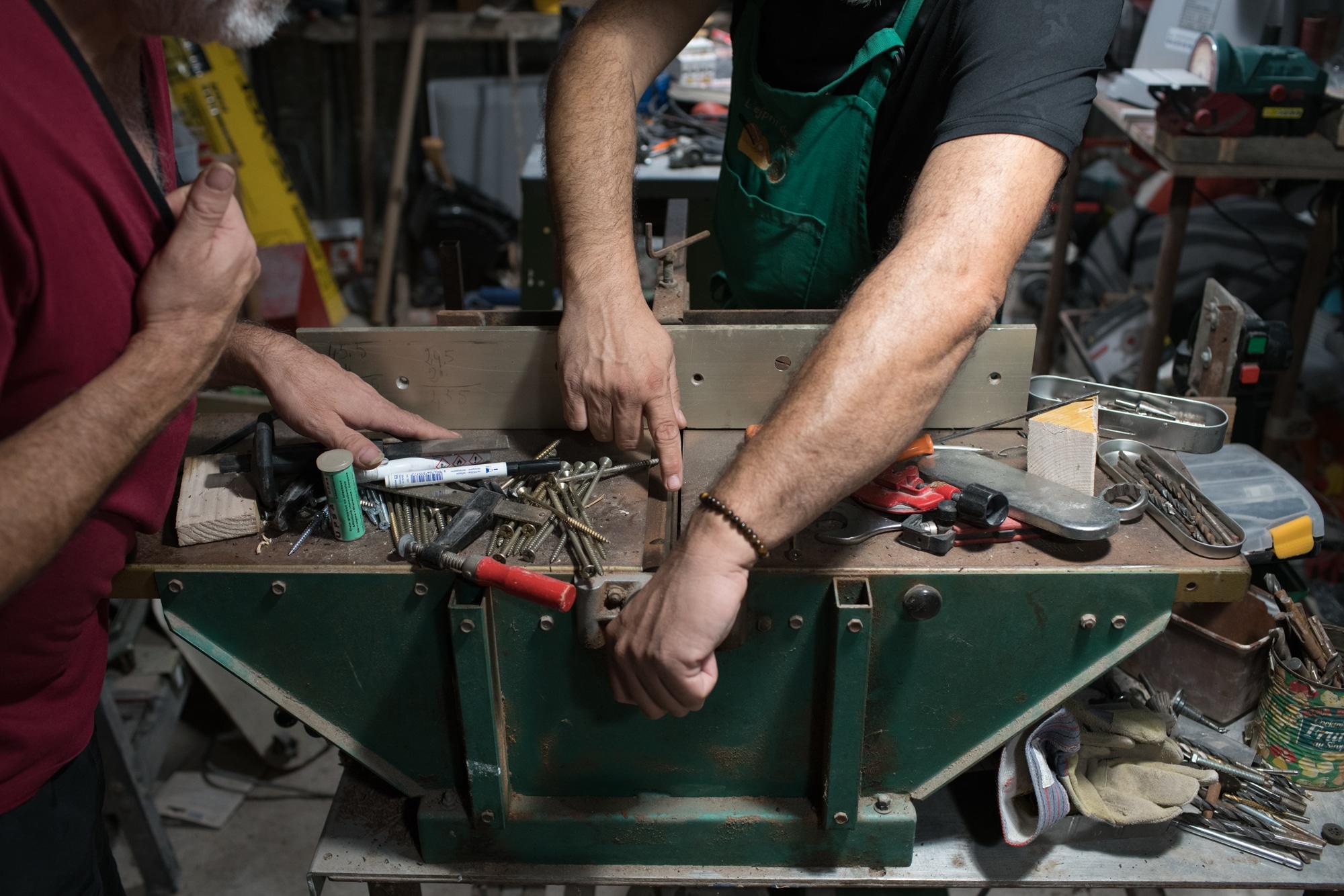 Quatre mains s'affairent autour d'un outil de conception.