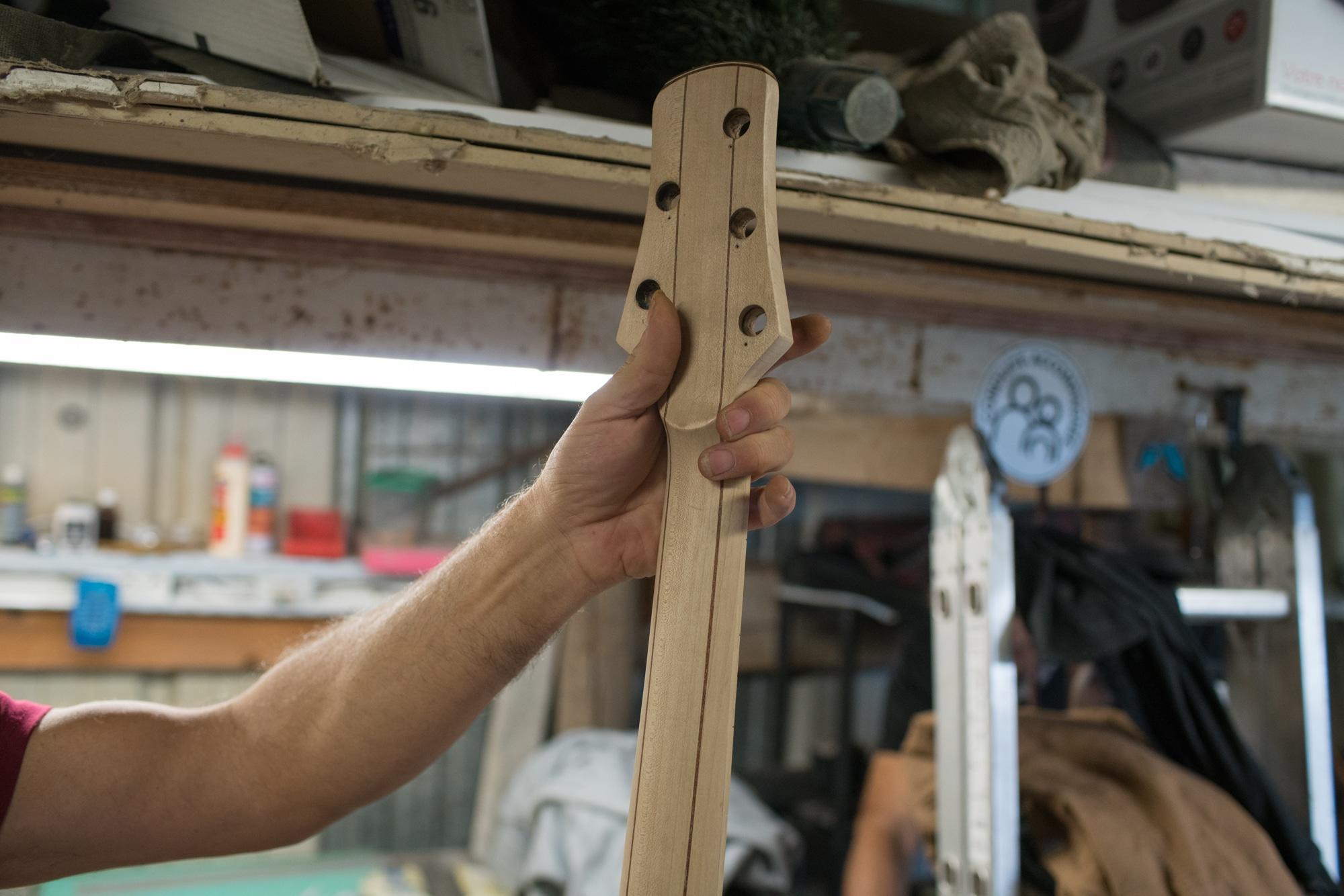 La main de Pierre saisit le haut d'un manche de guitare nu.