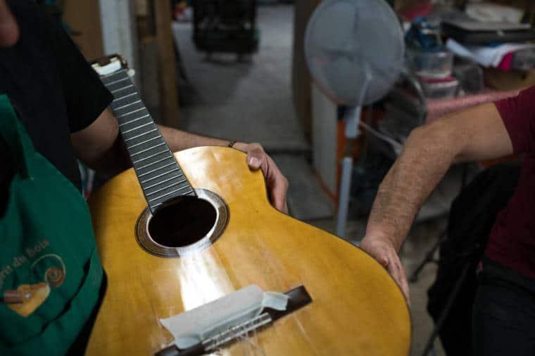 Pierre tient une guitare contre lui, tandis que la main d'un autre vient toucher le corps de la guitare.