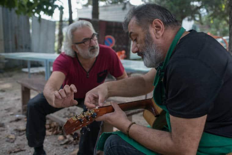 Pierre Cortes est penché sur sa guitare, en extérieur.