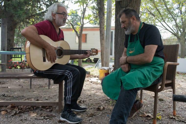 PIerre observe sa guitare, jouée par une autre personne, en extérieur.