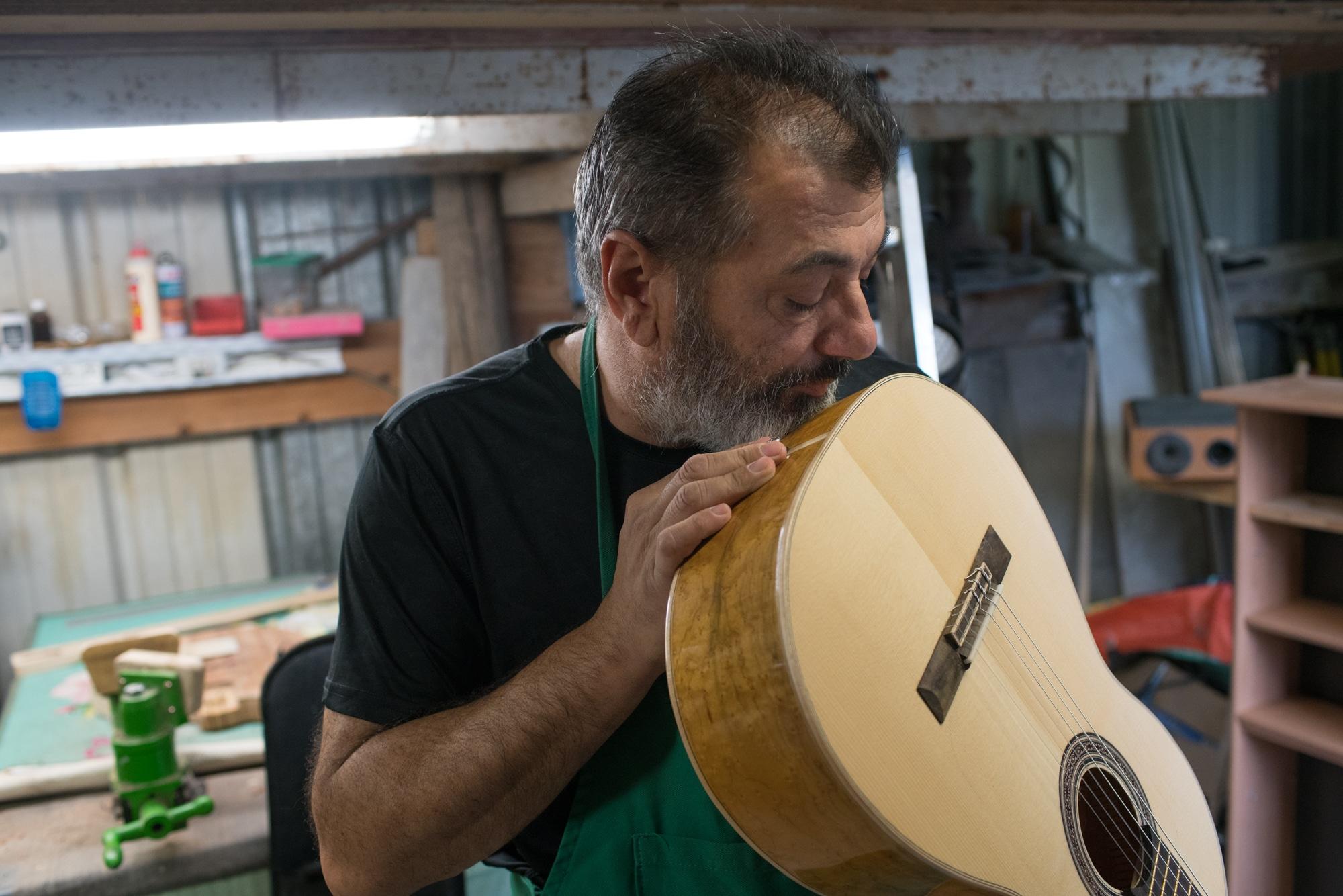 Pierre vérifie la courbure du manche en partant de la caisse de la guitare, dans son atelier.