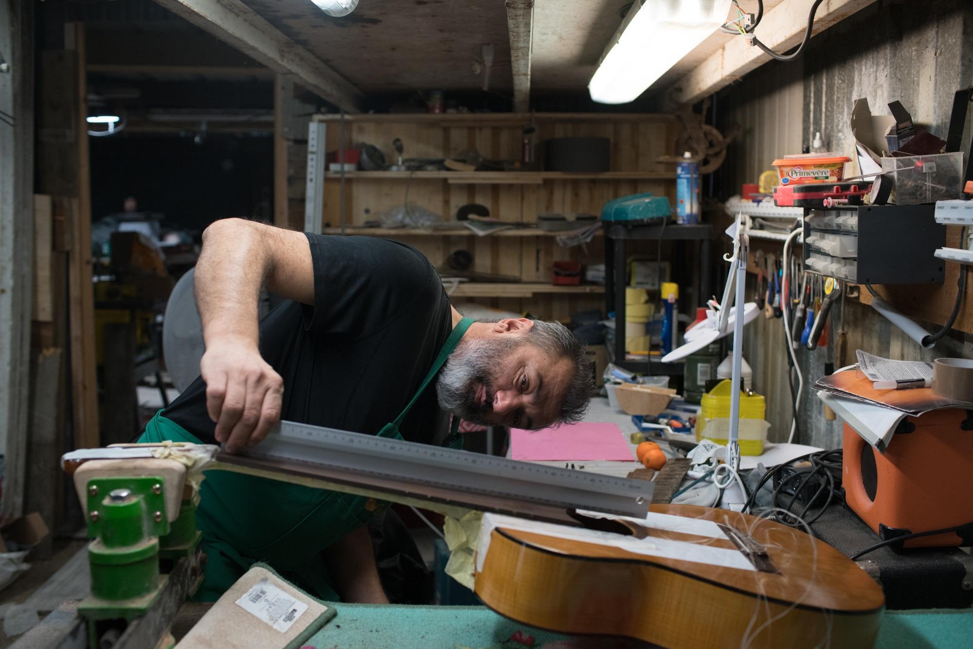 À l'aide d'une règle en fer, Pierre vérifie la courbure du manche de la guitare.