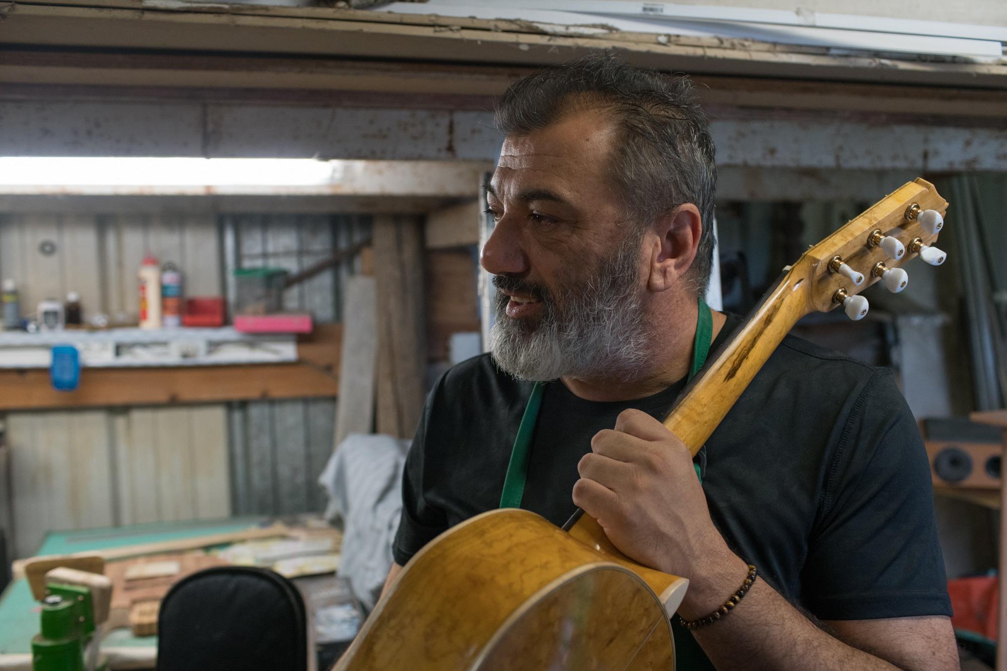 Pierre, une guitare dans la main gauche, dans son atelier.