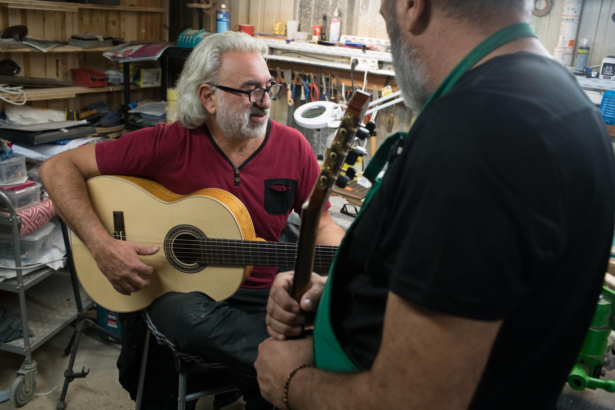 Pierre, tenant une guitare dans ses mains, observe une autre personne jouant sur sa guitare.
