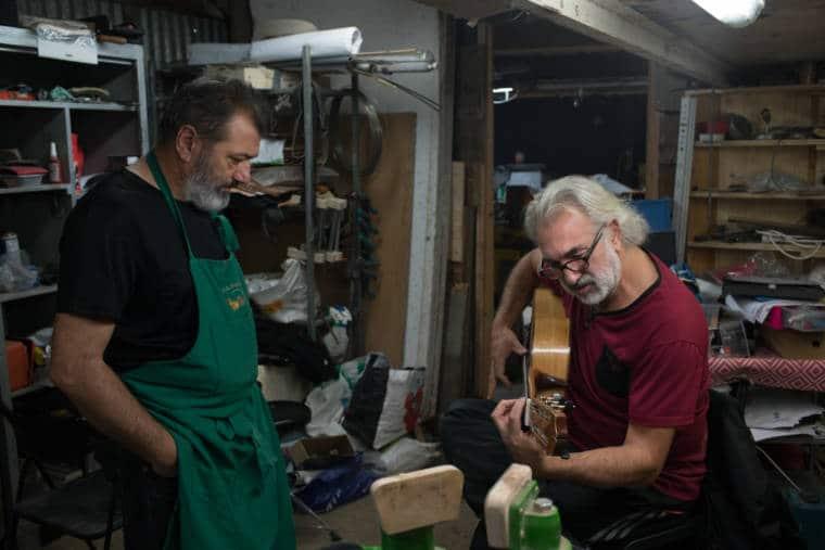 Pierre, debout, continue de regarder un homme jouer de la guitare.