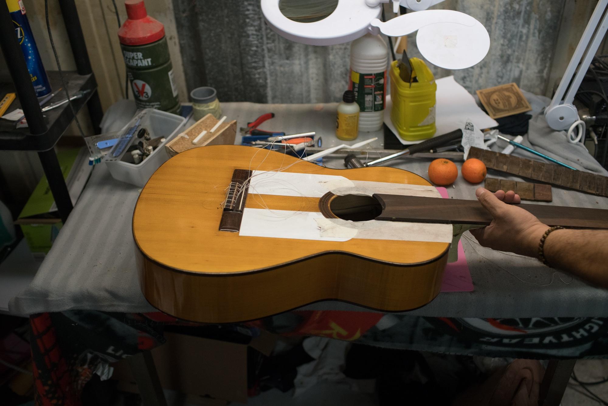Une guitare de Pierre en assemblage, posée sur son établi.