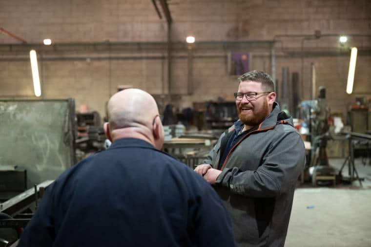 Arnaud échange avec un collaborateur en riant, dans un hangar