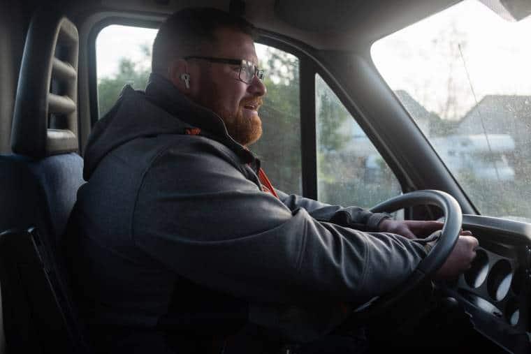 Équipé d'un kit mains libres, les deux mains posées en travers du volant, Arnaud est assis dans son camion et regarde au loin