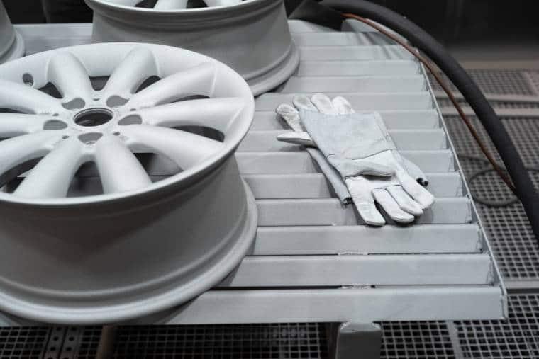 Deux gentes de voiture laquées reposent à côté de gants sur une structure métallique