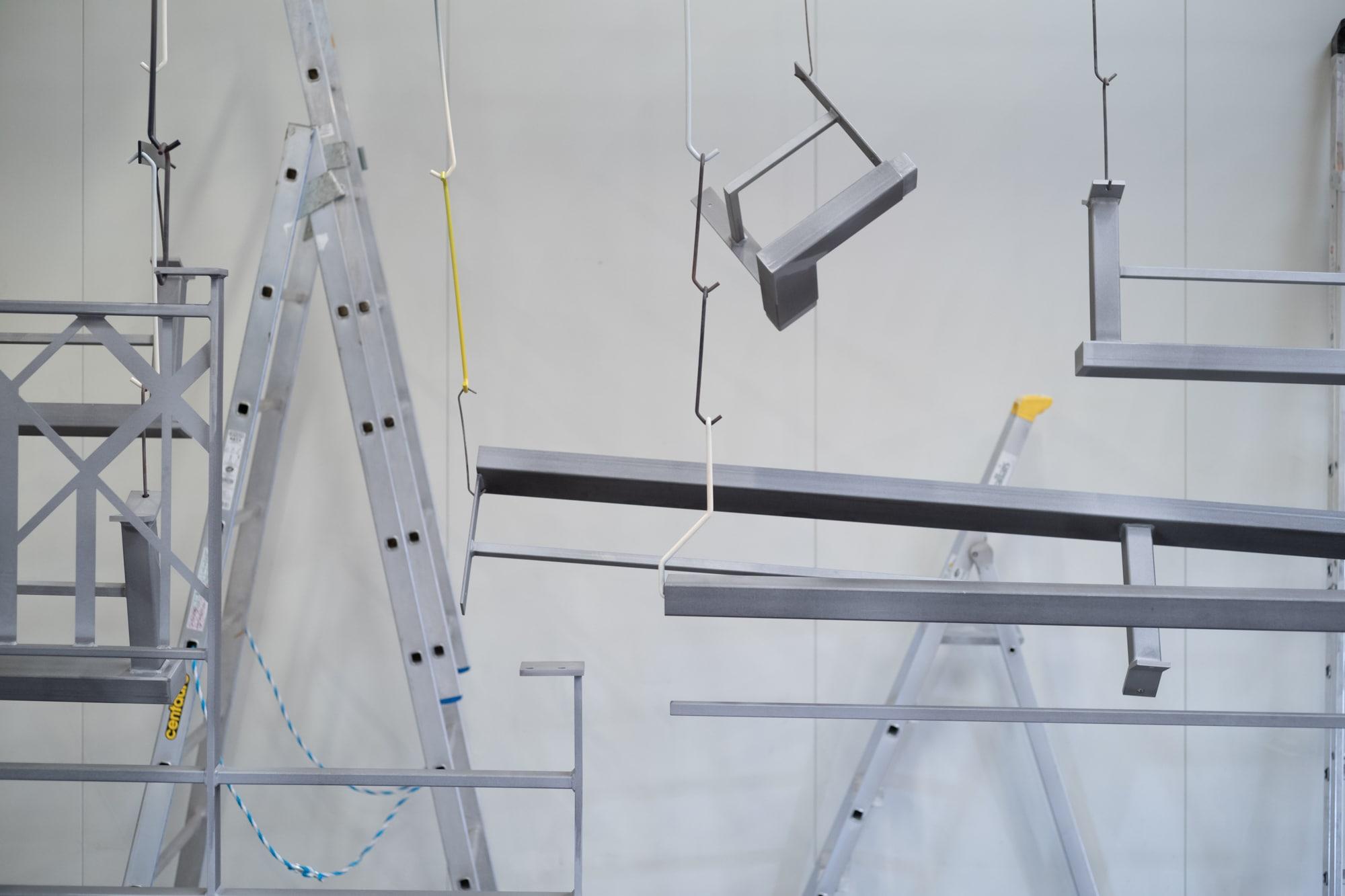 Différentes structures thermolaquées sont suspendues par des crochets sur un fond blanc
